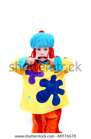 "Little boy dressed in clown costume is ""clowning around"" and making funny faces.  He is pulling his mouth from both sides to show his teeth. - stock photo"