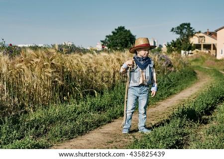 Little boy dressed in Western style in the field , retro style - stock photo