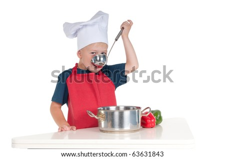 Little boy dressed like a chief tasting the food he made - stock photo