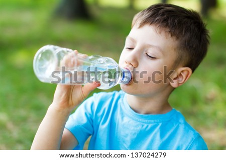Little boy drink water, outdoor - stock photo