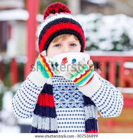 Little boy drinking chocolate drink with marshmallows, outdoors with snow background. Kid boy in winter sweater, hat, long warm scarf and colorful gloves. On cold snowy winter day. - stock photo