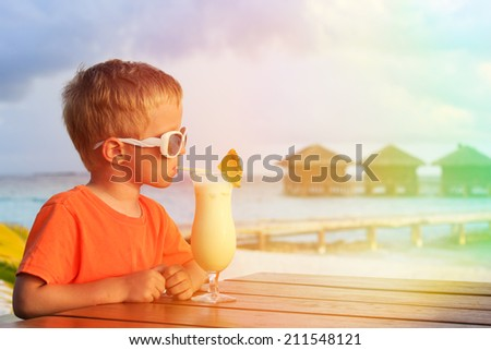little boy drinking cocktail on tropical beach vacation - stock photo