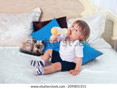 Little boy drinking milk from bottle on the bed - stock photo