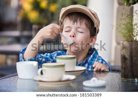 Little boy drinking milkshake in cafe - stock photo