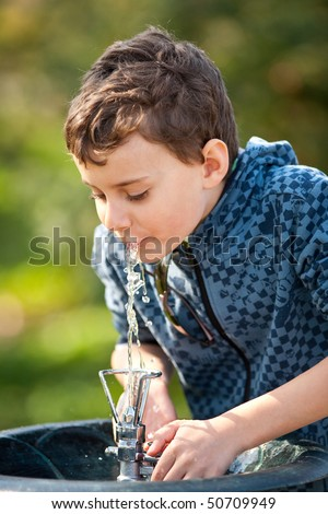 Little boy drinking water from a sprinkler in a park - stock photo