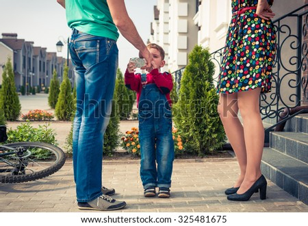 little boy drinking water from bottle in father's hands at home porch - stock photo