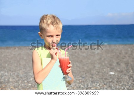 Little boy drinking water-melon juice at hot summer day on beach - stock photo