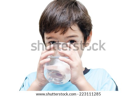 little boy drinks water from a glass - stock photo