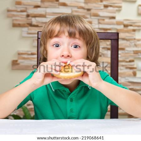 Little boy eat hamburger at the table - stock photo