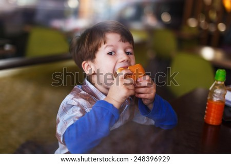 Little boy eat hamburger behind glass in fast food restaurant - stock photo