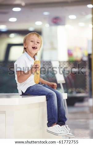 Little boy eating a baguette - stock photo