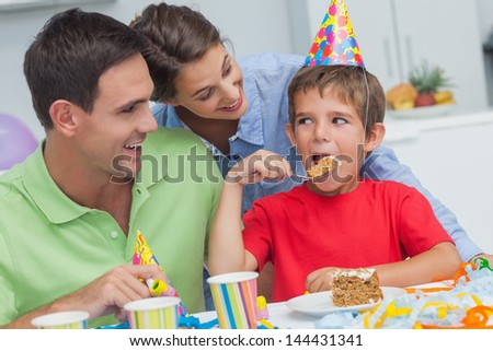 Little boy eating a birthday cake with parents during his birthday party - stock photo