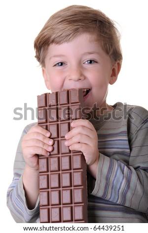 little boy eating a chocolate bar - studio portrait - stock photo