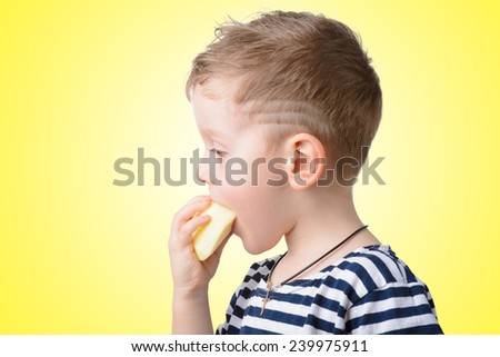 little boy eating an apple on a yellow background closeup - stock photo