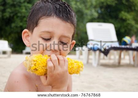 Little boy eating boiled corn - stock photo
