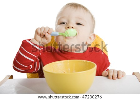 Little boy eating breakfast isolated on white.