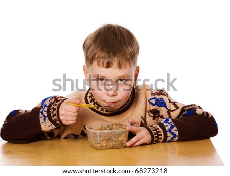 Little boy eating breakfast isolated on white