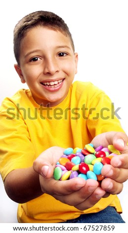 Little boy eating candy on white background. Little boy eating chicle. Little boy holding candies on white background. - stock photo