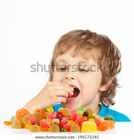 Little boy eating colored jelly candies on a white background - stock photo