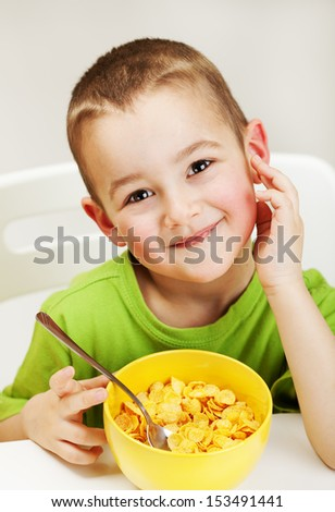 Little Boy eating cornflakes and smile - stock photo