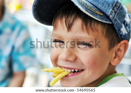 little boy eating french fries in cafe - stock photo