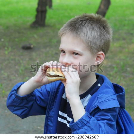 little boy eating hamburger in the park