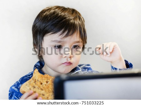 Little boy eating honey on toast watching his tablet with unhappy face, Spoiled children concept