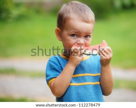 Little boy eating melon - stock photo