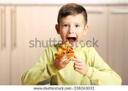 Little boy eating pizza at home - stock photo