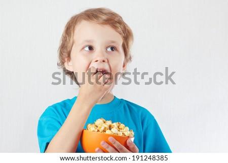 Little boy eating popcorn on a white background - stock photo