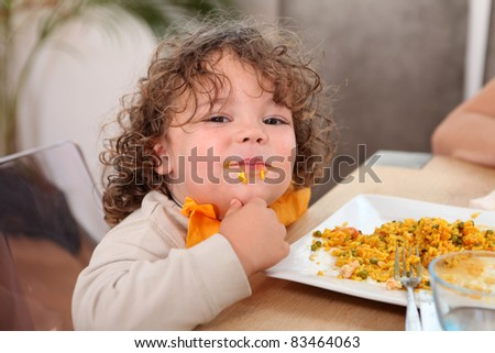 Little boy eating rice at kitchen table