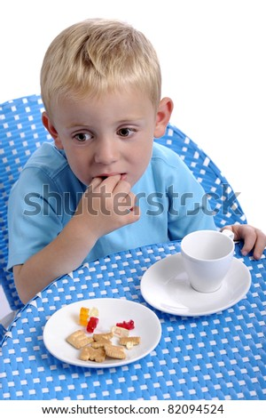 little boy eating sweeties and biscuits and drinking a cup of milk - stock photo