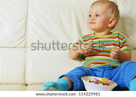 Little boy eating sweets. full bowl of candy