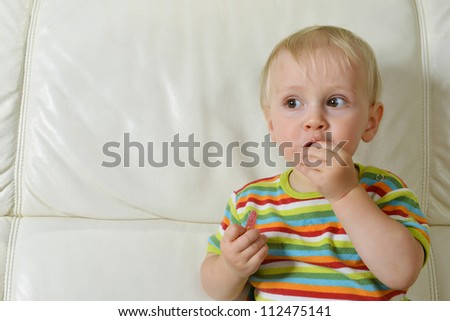 Little boy eating tasty candy - stock photo
