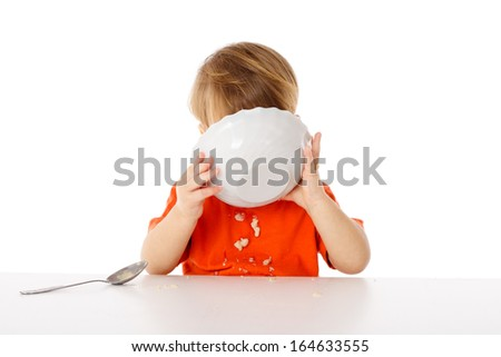 Little boy eating the oatmeal from a bowl, isolated on white