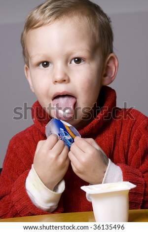 Little boy eating yogurt or yoghurt with a bit of it on his tongue