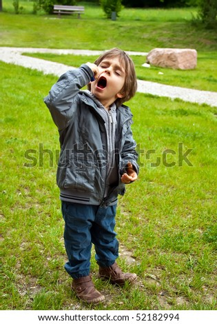 Little boy eats sweets. He covered his eyes with pleasure. - stock photo
