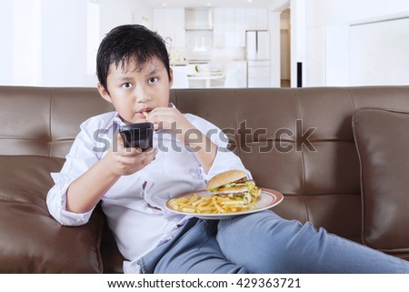 Little boy enjoying cheeseburger and french fries while sitting on the sofa and watching tv at home