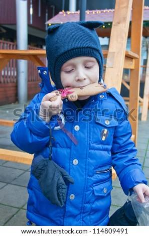 Little boy enjoying christmas gingerbread - stock photo