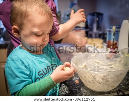 Little boy enjoying dough making in home kitchen - stock photo
