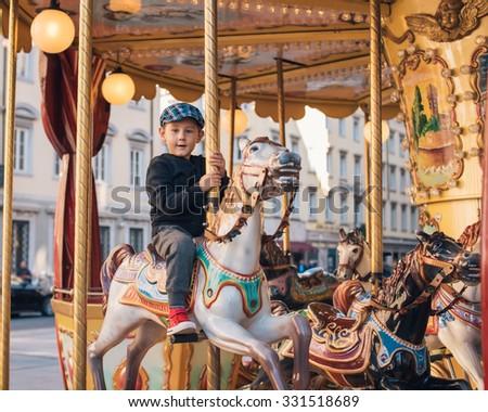 Little boy enjoying his ride at carousel in amusement park - stock photo