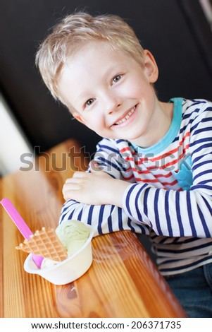 little boy enjoying ice cream in cafe - stock photo