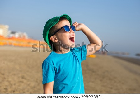 Little boy enjoying summer and shouting on beach - stock photo
