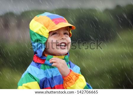 Little boy enjoying the rain dressed in a rainbow colored raincoat - stock photo
