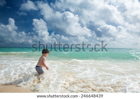 Little boy enjoys summer day at the tropical beach. - stock photo