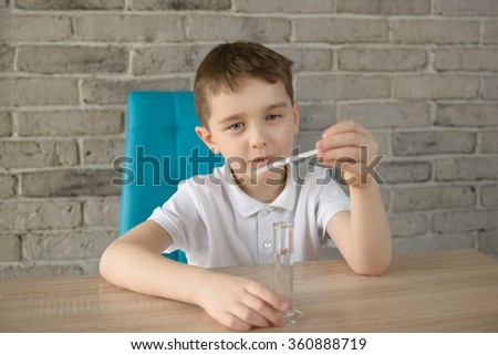 Little boy examines water at home. Checks its ph - stock photo