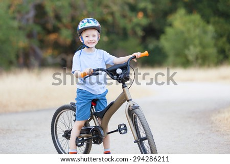 little boy excited to ride a bicycle in the park - stock photo