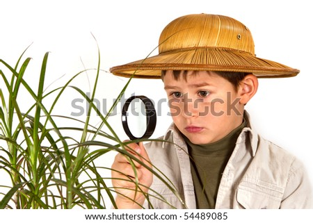 little boy explorer examining tropical plant with magnifying glass - stock photo