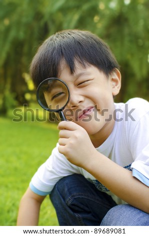 Little boy exploring nature by magnifier - stock photo