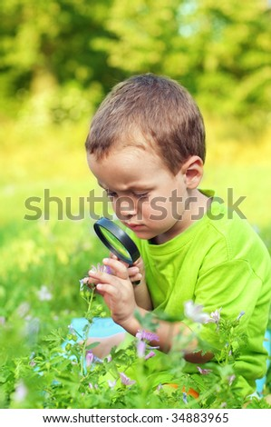 little boy exploring the nature through the magnifying glass - stock photo